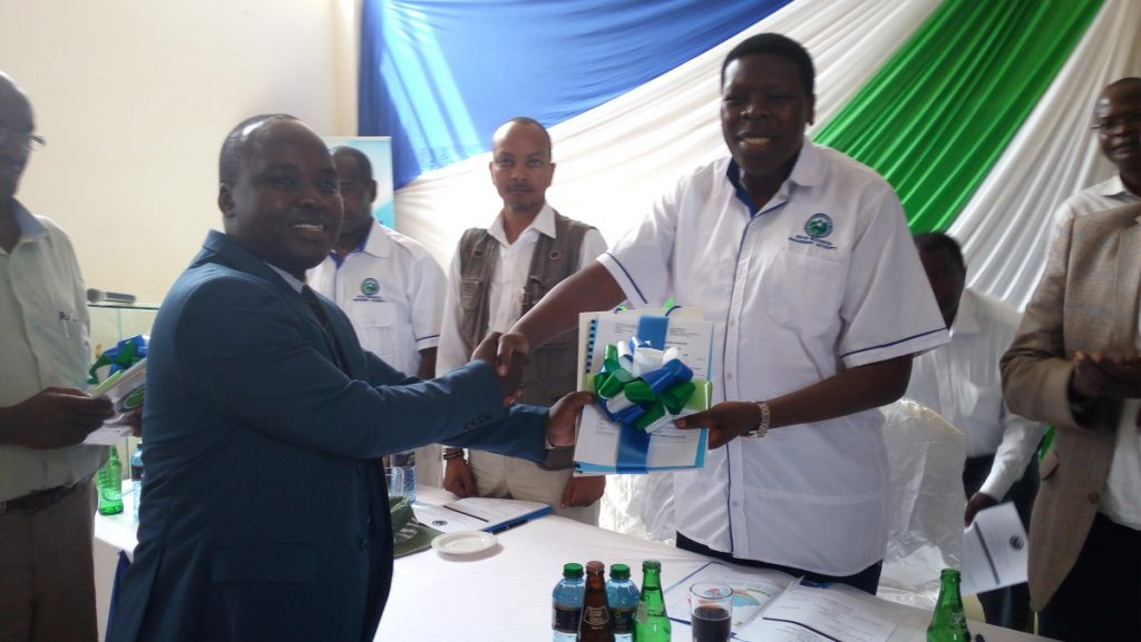 Hon. Eugene Wamalwa, former CS Ministry of Water and Irrigation handing over the finalized SCMP document and Certificate to Mr. Sebastian Njagi, WRUA Chairman South Maara WRUA SCMP launch of the South Maara and Ruguti WRUAs in Tana Basin Area.