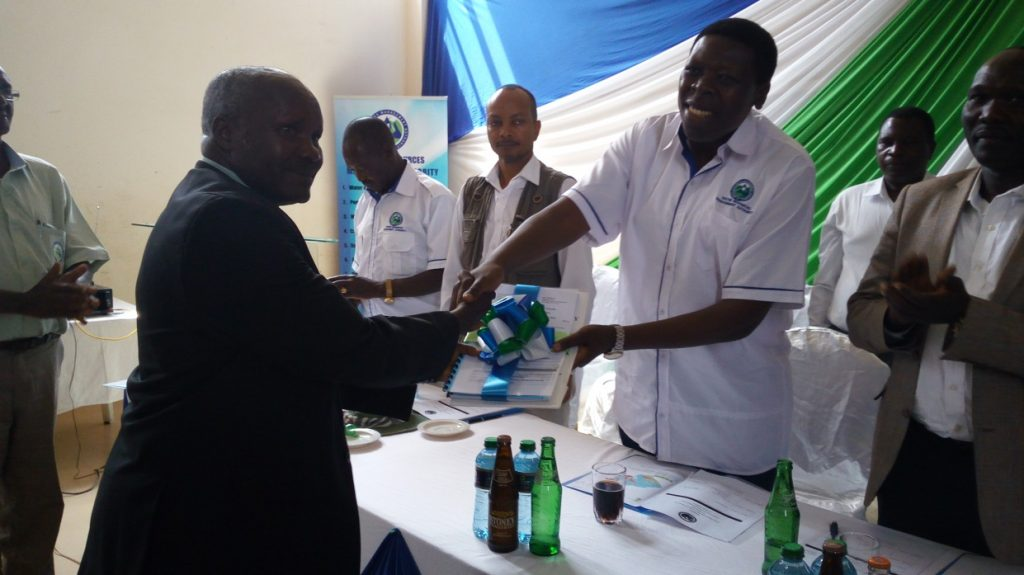 Hon. Eugene Wamalwa, former CS Ministry of Water and Irrigation handing over the finalized SCMP document to Mr. Jafford Njiru, WRUA Chairman Ruguti WRUA during the SCMP launch of the South Maara and Ruguti WRUAs in Tana Basin Area